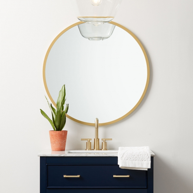 Matte gold rubber framed round mirror hanging on bathroom wall above navy vanity