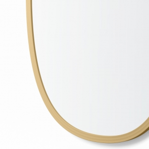 Close-up angle shot of matte gold rubber framed oval mirror
