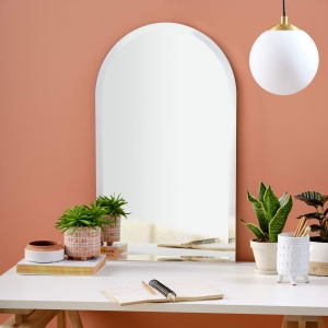 Frameless beveled arch-top cathedral mirror resting on home office desk