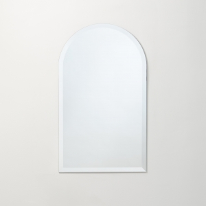 Frameless beveled arch-top cathedral mirror hanging on beige wall
