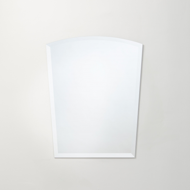 Frameless beveled arch-top concave mirror hanging on beige wall