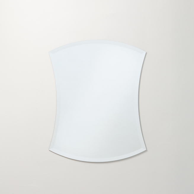 Frameless beveled arch-top hourglass mirror hanging on beige wall