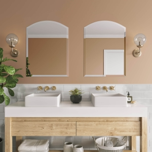 Frameless beveled arch-top mirrors hanging on bathroom wall above double sink vanity