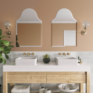 Two frameless beveled bell-top mirrors hanging on bathroom wall above double-sink vanity