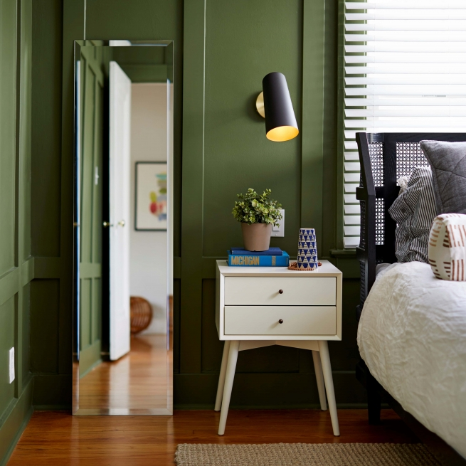 Frameless beveled full-length rectangle mirror hanging on bedroom wall near bed and side table