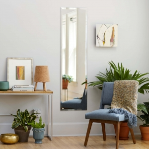 Frameless beveled full-length rectangle mirror hanging on living room wall near chair and side table