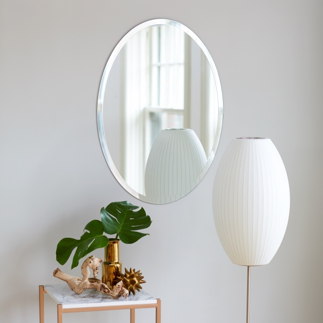 Frameless beveled oval copper-free mirror hanging on wall near lamp
