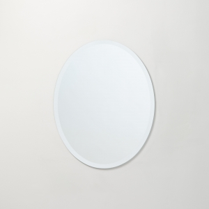 Frameless beveled oval copper-free mirror hanging on beige wall