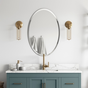 Frameless beveled oval mirror hanging on bathroom wall above muted teal vanity