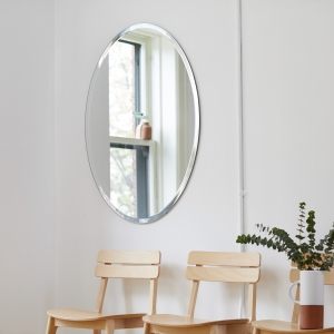 Frameless beveled oval mirror hanging on wall above chairs