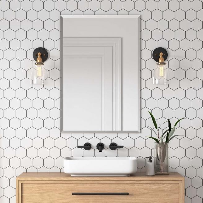 Frameless beveled rectangle mirror hanging on modern bathroom tile wall above vanity