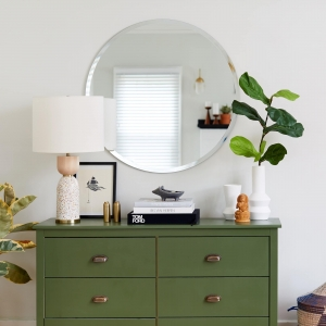 Frameless beveled edge round mirror mounted on the wall above a green credenza in a living room