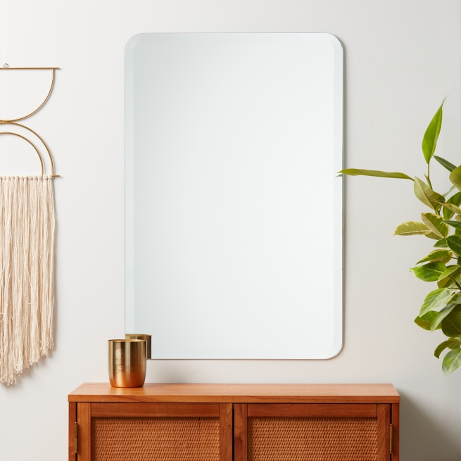 Frameless beveled rounded rectangle mirror hanging on wall above credenza