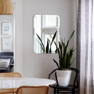 Frameless beveled edge rounded rectangle mirror hanging on a wall in a dining room