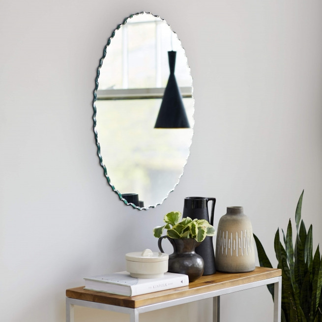 Frameless chiseled edge oval mirror hanging on wall above sideboard and plant