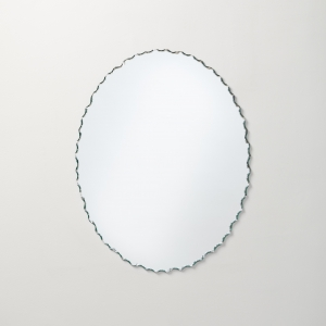 Frameless chiseled edge oval mirror hanging on beige wall