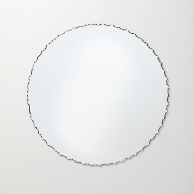 Frameless chiseled edge round mirror hanging on beige wall