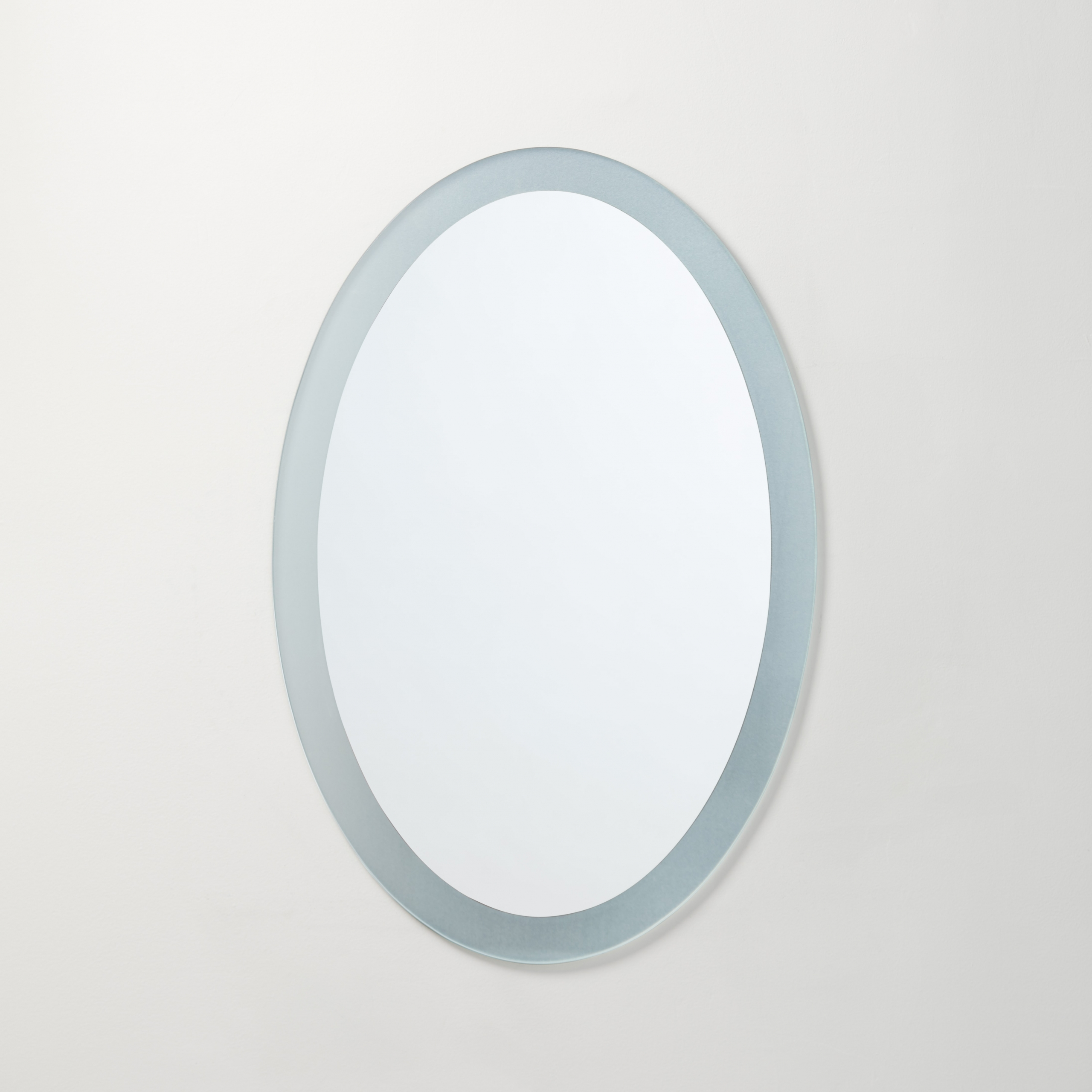 Frosted border frameless mirror hanging on beige wall