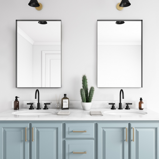 Black metal framed rectangle mirrors hanging on bathroom wall above double sink vanity