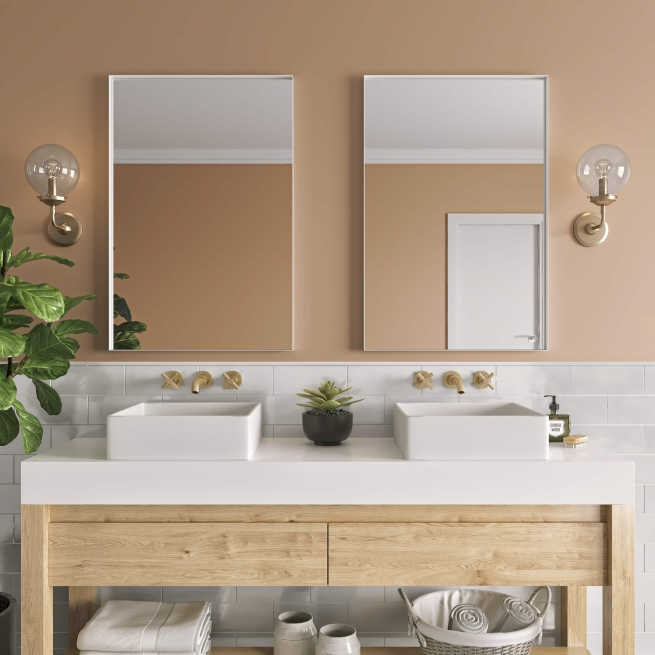 White metal framed rectangle mirrors hanging on bathroom wall above double sink vanity
