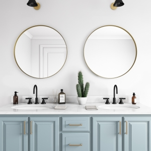 Gold metal framed round mirrors hanging on bathroom wall above double sink vanity