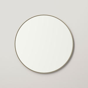 Gold metal framed round mirror hanging on beige wall