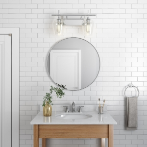 Silver metal framed round mirror hanging on bathroom wall above single sink vanity