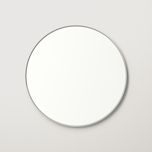 Silver metal framed round mirror hanging on beige wall