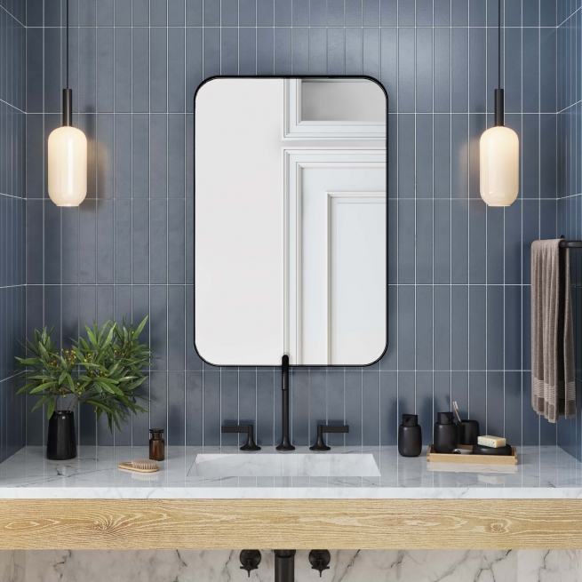 Black metal framed rounded rectangle mirror hanging on bathroom wall above single sink vanity