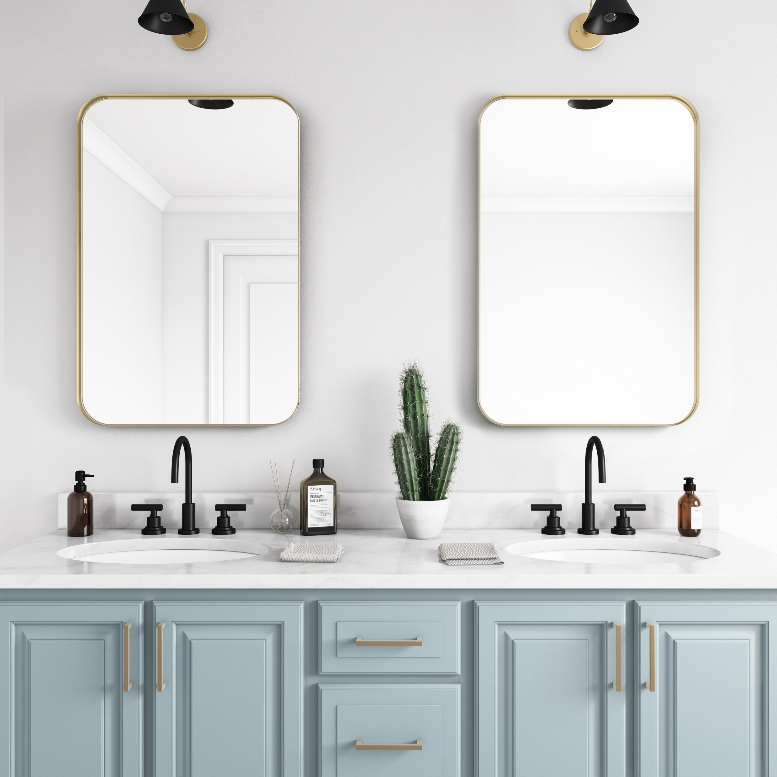 Gold metal framed rounded rectangle mirrors hanging on bathroom wall above double sink vanity