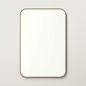 Gold metal framed rounded rectangle mirror hanging on beige wall