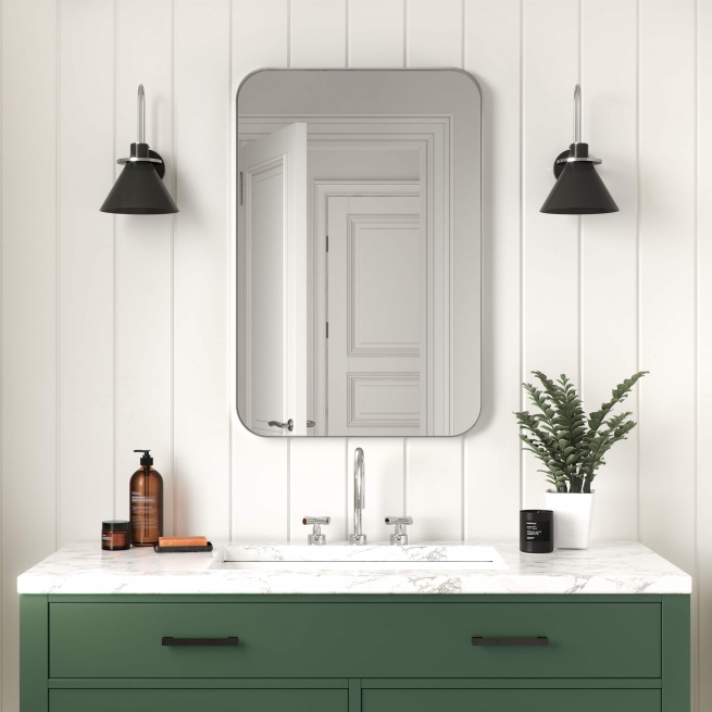 Silver metal framed rounded rectangle mirror hanging on bathroom wall above single sink vanity