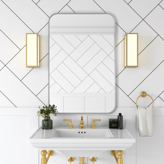 White metal framed rounded rectangle mirror hanging on bathroom wall above single sink vanity