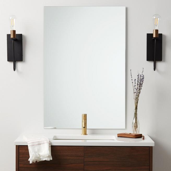 Frameless polished edge rectangle mirror hanging on bathroom wall above single sink wood vanity