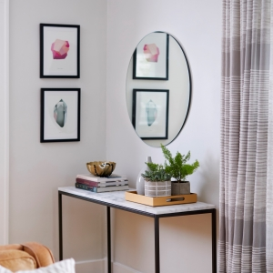Polished edge round mirror hanging on living room wall above modern sideboard