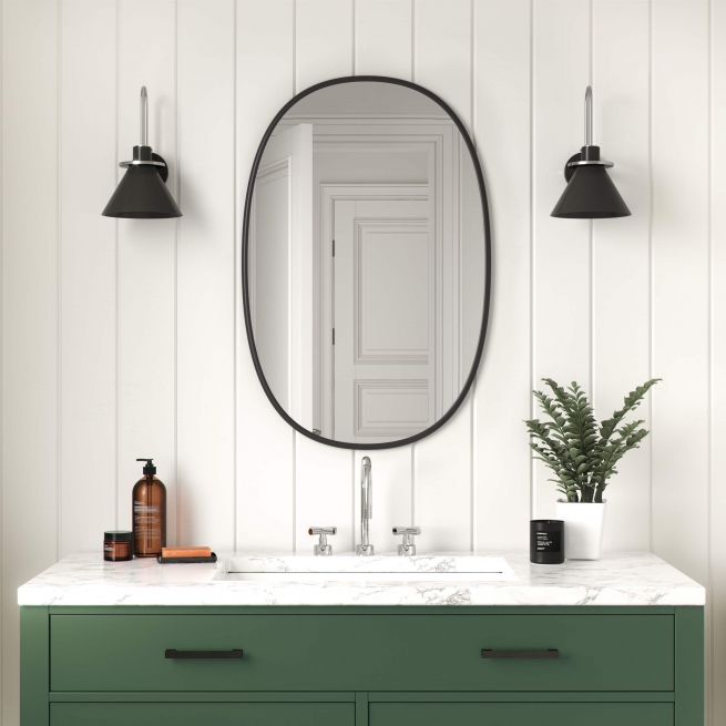 Black rubber framed oval mirror hanging on bathroom wall above green vanity
