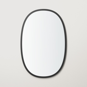 Black rubber framed oval mirror hanging on beige wall