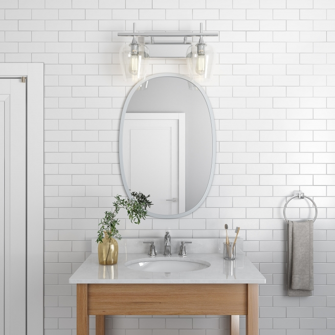 Grey rubber framed oval mirror hanging on bathroom wall above wood vanity