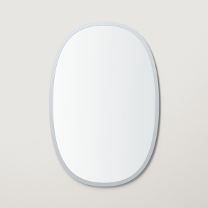 Grey rubber framed oval mirror hanging on beige wall