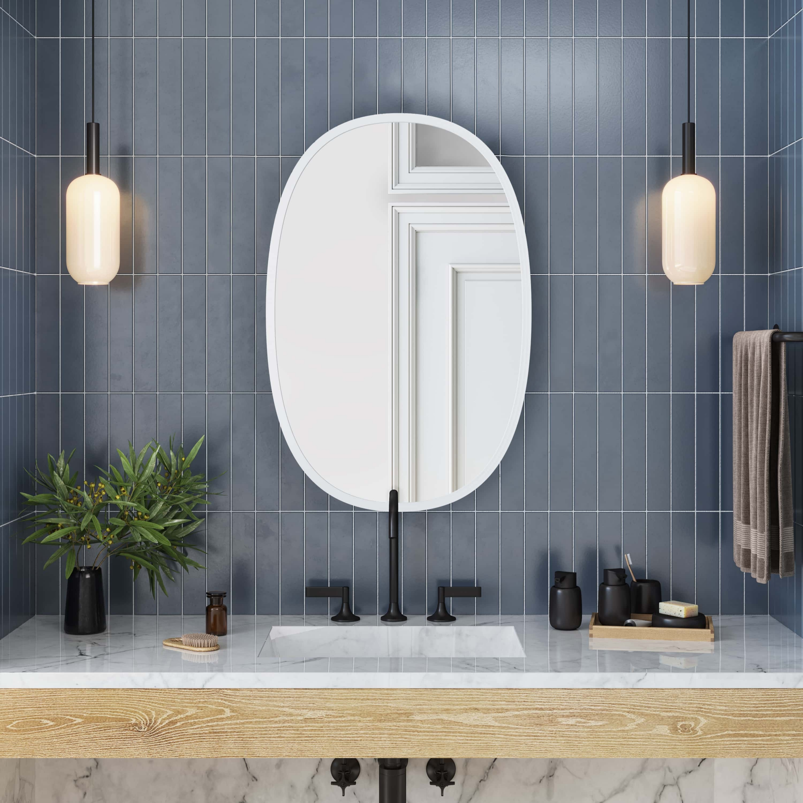 White rubber framed oval mirror hanging on blue tiled bathroom wall above vanity
