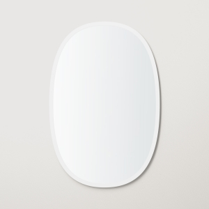 White rubber framed oval mirror hanging on beige wall