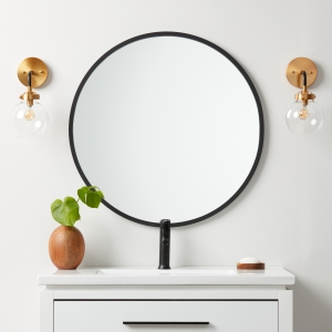 Black rubber framed round mirror hanging on bathroom wall above vanity