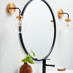 Angled view of black rubber framed round mirror hanging on bathroom wall above vanity