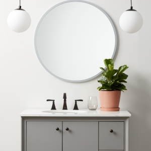 Grey rubber framed round mirror hanging on bathroom wall above vanity