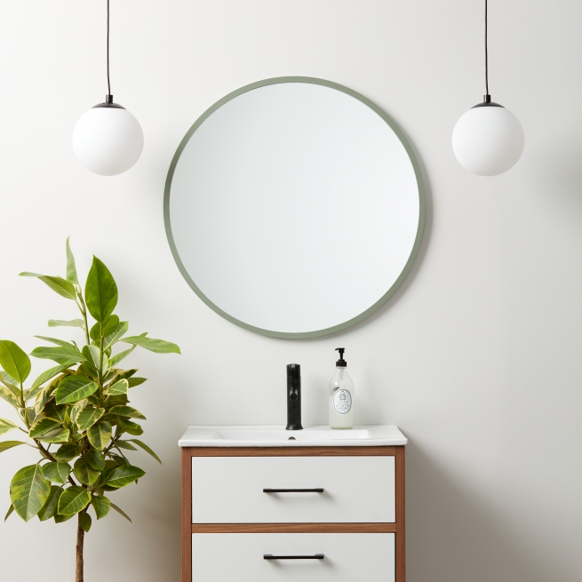 Sage green rubber framed round mirror hanging on bathroom wall above vanity