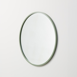 Angled view of sage green rubber framed round mirror