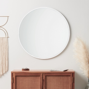 White rubber framed round mirror hanging on bathroom wall above credenza