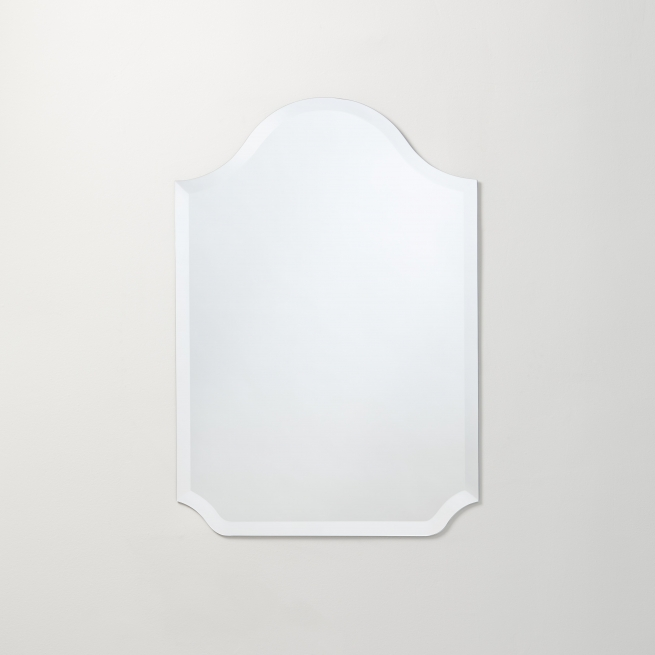 Frameless scalloped bell-top mirror hanging on beige wall