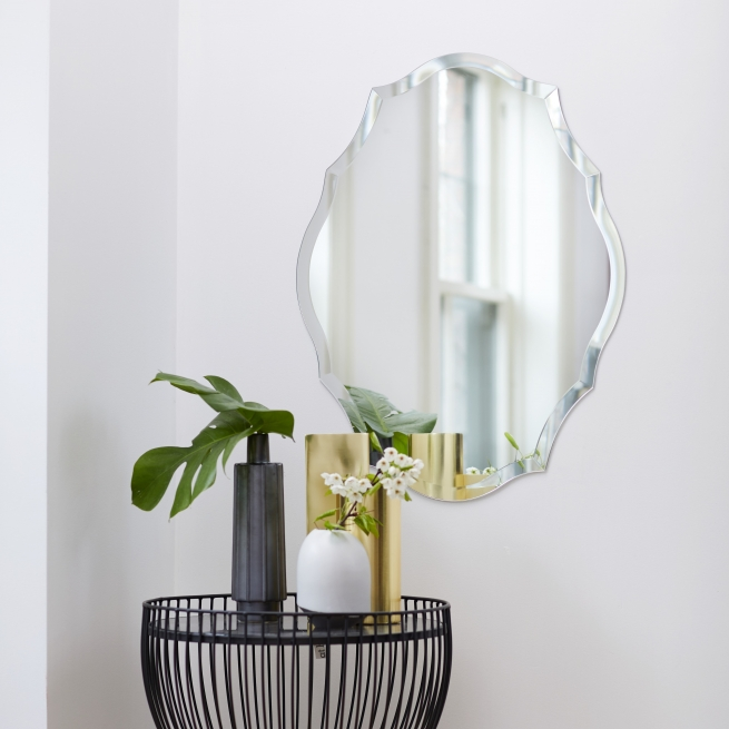 Frameless scalloped oval mirror hanging on wall near side table