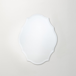 Frameless scalloped oval mirror hanging on beige wall